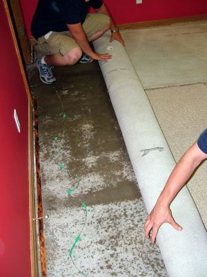Hanover water damaged carpet being removed by two men.